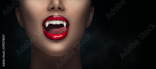 Sexy Vampire Woman's red bloody lips close-up. Vampire girl licking fangs with tongue. Fashion Glamour Halloween art design. Close up of female vampire mouth, teeth. Isolated on black background - 291378037