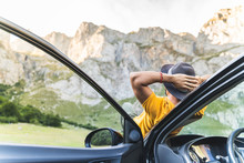 Man Laid Down On The Car Bonnet While Enjoy The Views Of Nature.