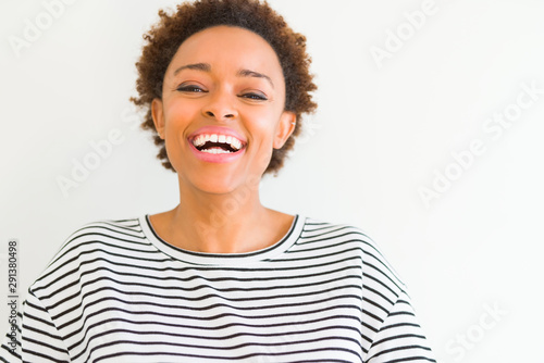 Beautiful young african american woman smiling confident to the camera showing teeth over isolated white background