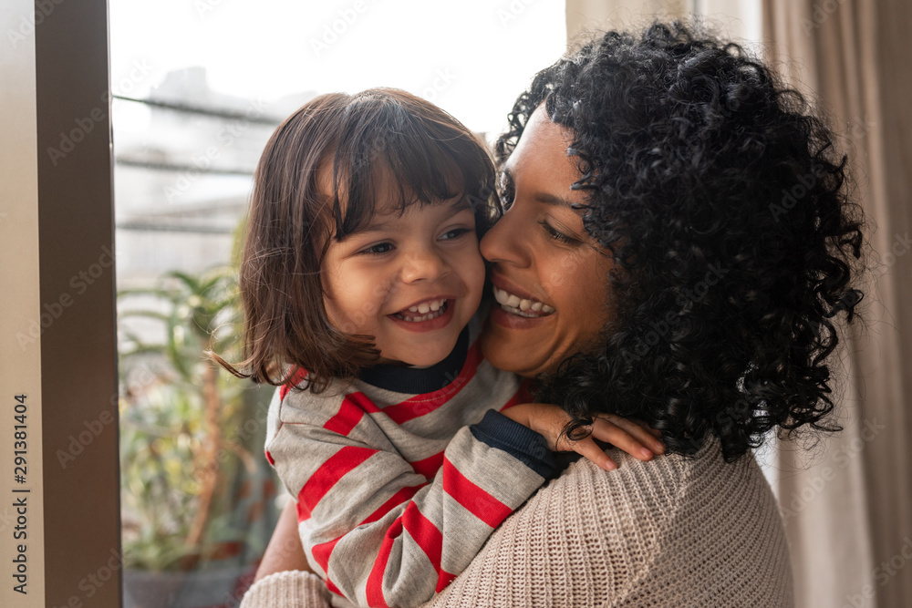 Fototapeta Loving mother hugging her cute little daughter at home
