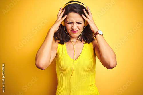 Young beautiful woman listening to music using headphones over yellow isolated background suffering from headache desperate and stressed because pain and migraine. Hands on head. - 291381894