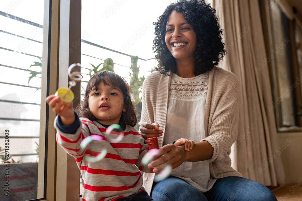 Fototapety, obrazy: Little girl and her mother playing with a bubble wand