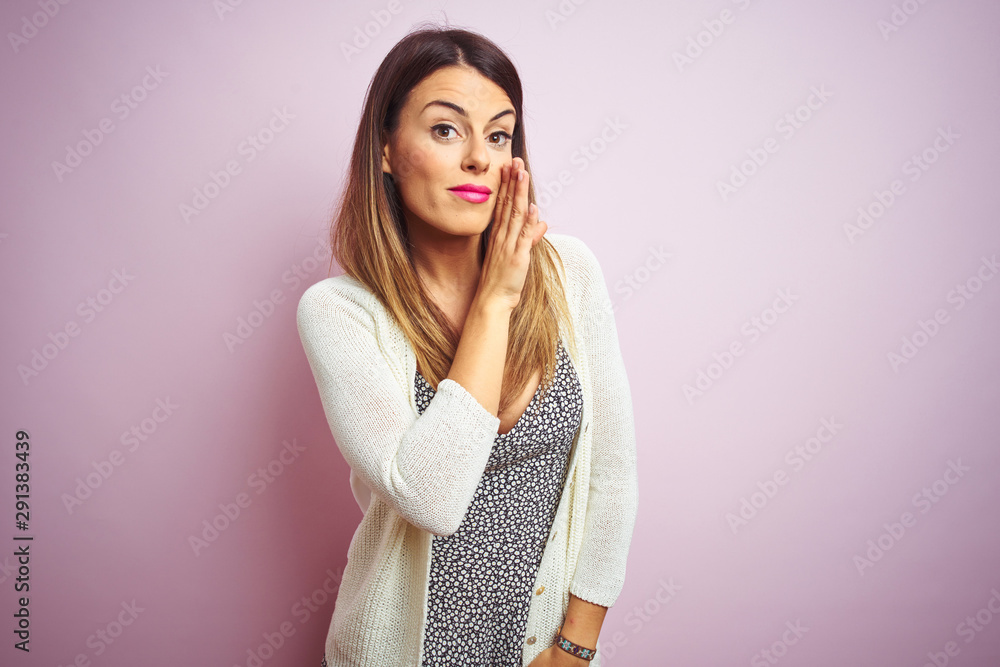 Fototapety, obrazy: Young beautiful woman standing over pink isolated background hand on mouth telling secret rumor, whispering malicious talk conversation