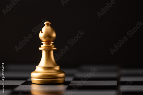 Fotografia gold bishop on the chess board