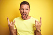 Young handsome man wearing casual yellow t-shirt over yellow isolated background shouting with crazy expression doing rock symbol with hands up. Music star. Heavy concept.