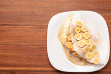 Tapioca Filled With Banana, Cinnamon And Condensed Milk, On Wooden Background. Flatbread Made From Cassava (also Known As Casabe, Bammy, Beiju, Bob, Biju).
