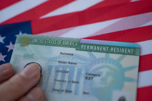 Permanent Resident Green Card  Of United States Of America On Flag Of USA. Above Close Up View.
