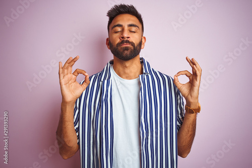 Deurstickers Ontspanning Young handsome indian man wearing summer striped shirt over isolated pink background relax and smiling with eyes closed doing meditation gesture with fingers. Yoga concept.