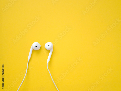 White earphones on yellow background. Earphones for listening to music and sound on portable devices. - 291394415