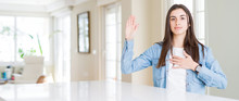 Wide Angle Picture Of Beautiful Young Woman Sitting On White Table At Home Swearing With Hand On Chest And Open Palm, Making A Loyalty Promise Oath
