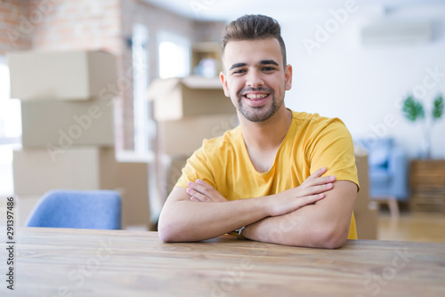 Fotografía  Young man sitting on the table with cardboard boxes behind him moving to new home happy face smiling with crossed arms looking at the camera