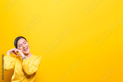 Woman in love showing heart isolated over yellow background Canvas Print