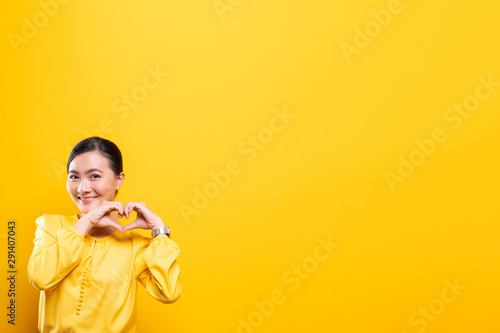 Photo Woman in love showing heart isolated over yellow background