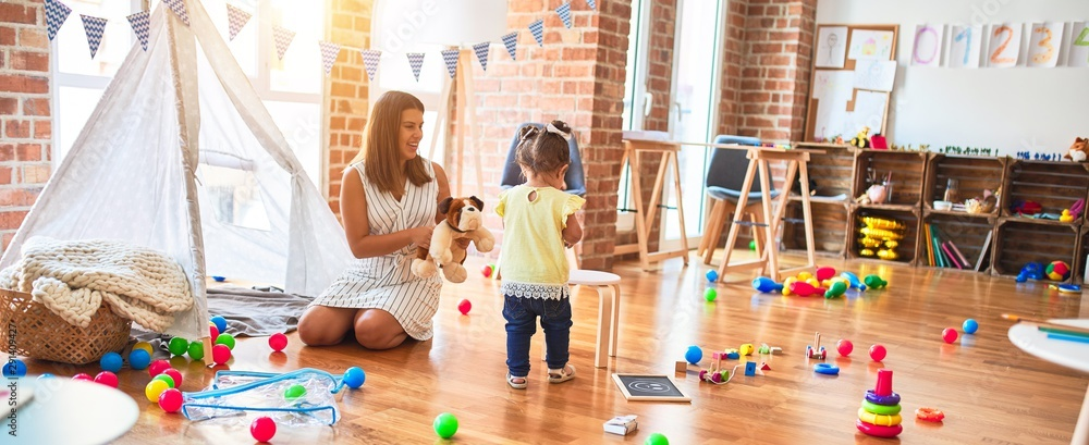 Fototapety, obrazy: Young beautiful teacher playing with dog doll and toddler holding jar of chocolate balls at kindergarten