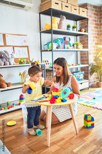 Obraz Young beautiful teacher and toddler playing with dishes, cutlery and cups toy on the table at kindergarten - fototapety do salonu