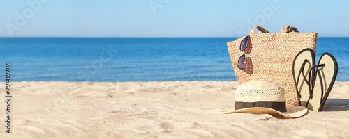 Stylish beach accessories on sandy sea shore. Banner design