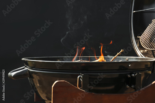 Fotografiet  New modern barbecue grill with burning firewood on dark background