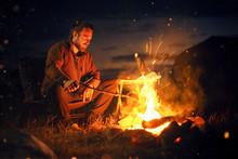 Man Sitting Next To A Bonfire In The Dark