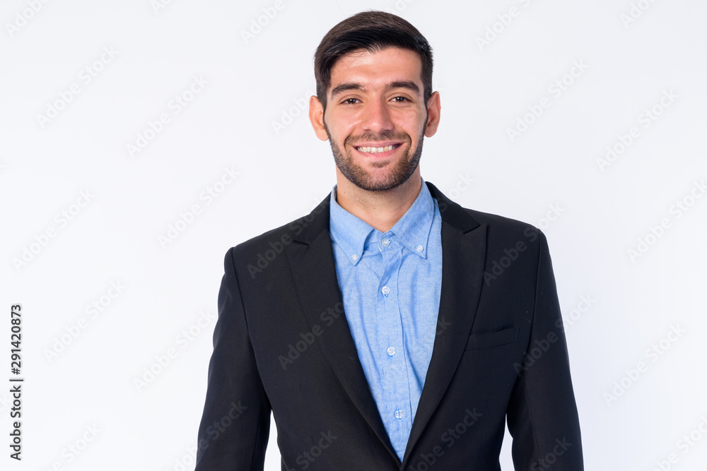 Fototapeta Portrait of happy young bearded Persian businessman in suit smiling