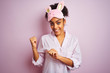 Young african american woman wearing pajama and mask over isolated pink background Pointing to the back behind with hand and thumbs up, smiling confident