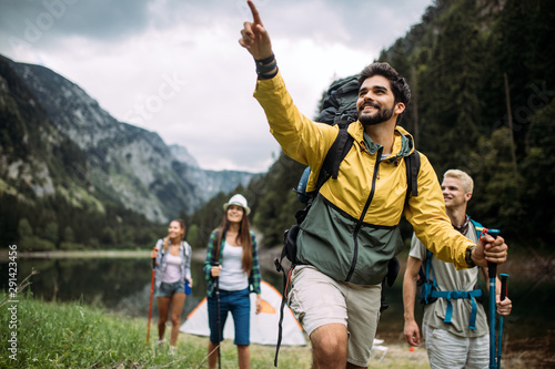 Obraz Group of happy friends with backpacks hiking together - fototapety do salonu