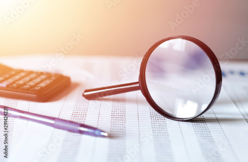 Single Magnifying Glass with Black Handle, Leaning on the financial data Wallpaper Mural