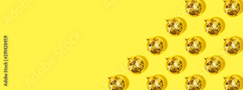 Creative Christmas pattern. Shiny gold disco balls over yellow background. Flat lay, top view. New year baubles, star sparkles. Party time. Cristmas greeting card - 291428459