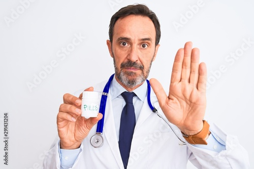 Fényképezés  Middle age doctor man holding pills standing over isolated white background with