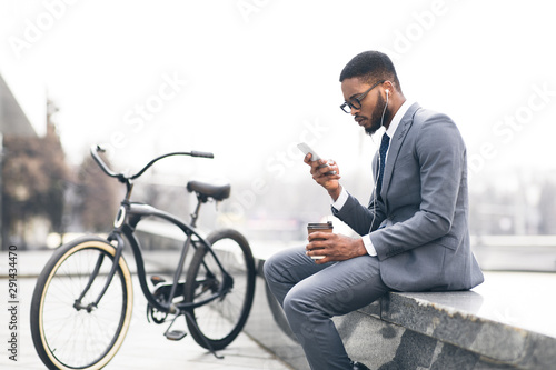 Afro businessman listening music and drinking coffee with bike nearby - 291434470