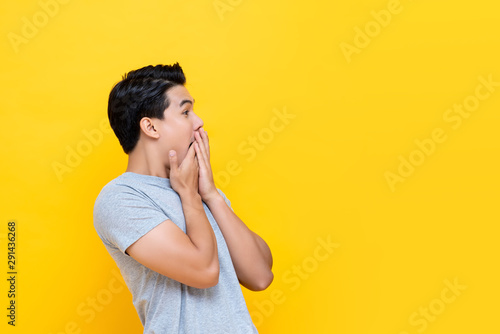 Young handsome excited Asian man with hands covering mouth Canvas-taulu