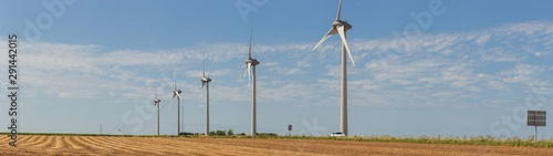 Fototapeta Panoramic view of wind turbines for electrical power generation in agricultural fields. Countryside in France. Renewable energy sources, industrial agriculture concept.   obraz
