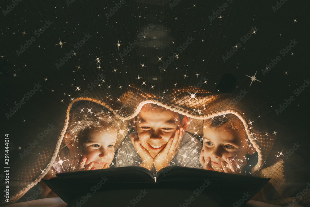 Fototapeta children reading a book under a blanket with light