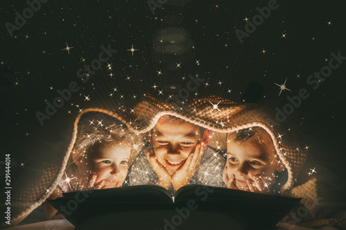 children reading a book under a blanket with light