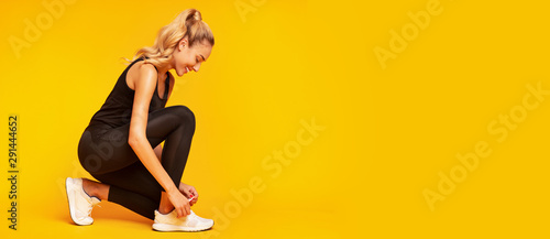 Young Woman Lacing Shoes Before Training In Studio, Panorama