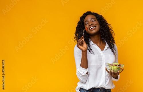 Photo Happy african american woman enjoying vegetable salad