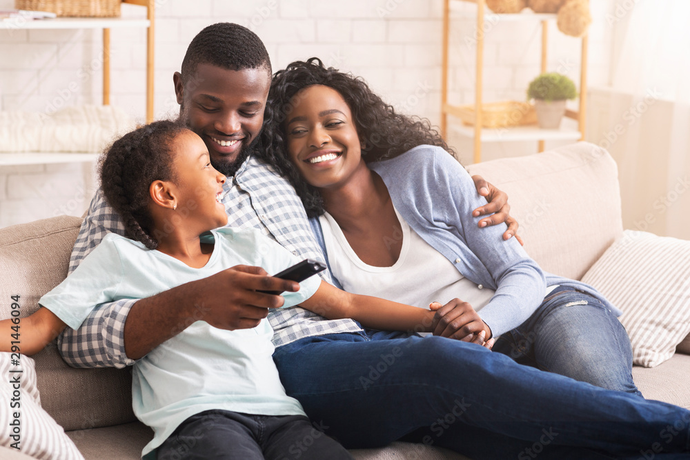 Fototapeta Happy african american family relaxing and watching TV at home