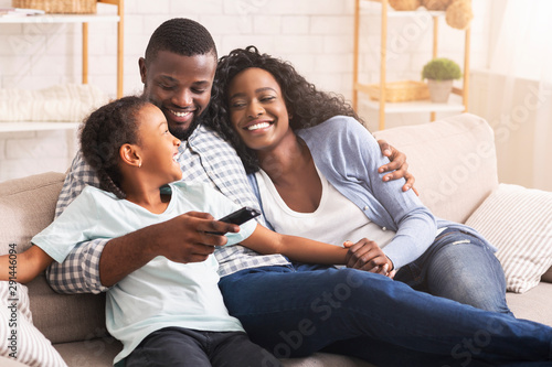 Fototapeta Happy african american family relaxing and watching TV at home obraz