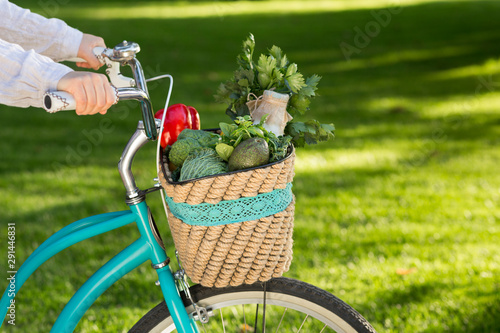 Obraz na plátně  Woman riding on bike with fresh farm vegetables