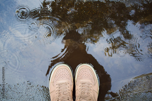 Fotografija female legs in sneakers stand in a rain puddle