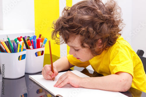 Valokuvatapetti Lovely curly-headed boy in yellow t-shirt writes copy-books, letters