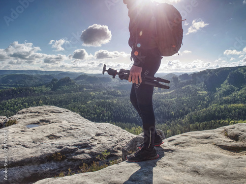 Wild nature photographer or traveler with tripod on stone Canvas-taulu