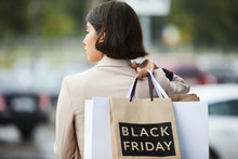 Back View Portrait Of Stylish Young Woman Holding Shopping Bags With Black Friday While Leaving Mall, Copy Space