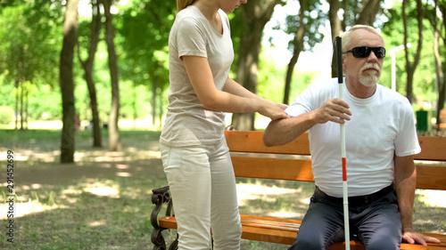 Fotografie, Tablou Female volunteer helping blind pensioner outdoors, social programs, support