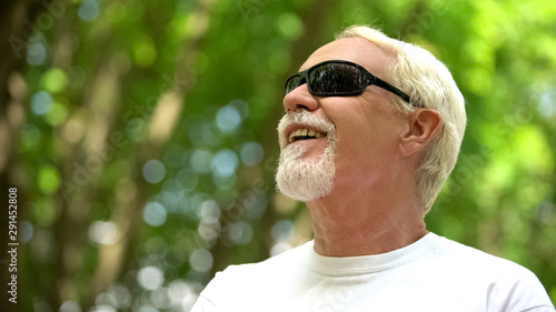 Visually impaired man in sunglasses listening nature sounds, heightened senses Canvas-taulu