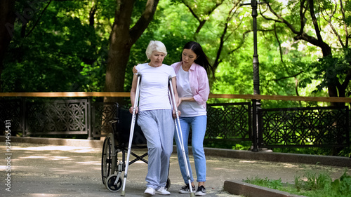 Valokuvatapetti Young woman helping old lady walking on crutches, hip fracture rehabilitation