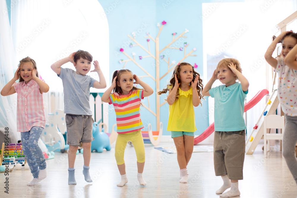 Fototapety, obrazy: Happy kids having fun dancing indoors in a sunny room at day care or entertainment center
