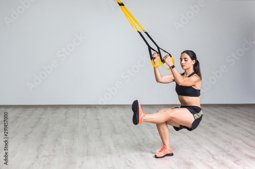 Portrait of young athletic woman in sportswear doing squat exercise, training legs and glutes muscular with fitness straps in the gym Fototapet