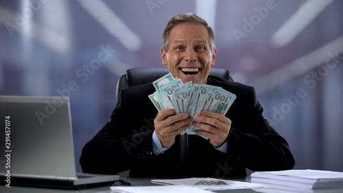 Obraz na plátne Cheerful manager holding dollar banknotes, rejoicing successful profitable deal