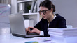 Woman typing on laptop, pile of documents lying on table, overload of work