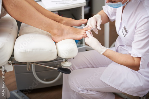 Pedicurist using stainless scissors while doing pedicure for young lady